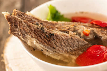 Shorpo in a white plate with a piece of beef meat in a broth with vegetables close up