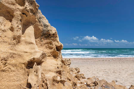 View of the turquoise waters of the Mediterranean Sea through sand formations on the shore against the blue sky