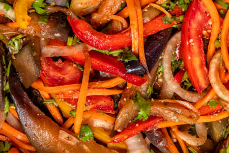 Top view on vegetable salad of eggplant, carrots, onions, peppers with oriental spices close-up