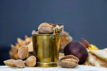 Still life with brass bucket and almond nuts close-up on blurred background