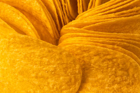 Mouth watering gold slices of potato chips or crisps close up