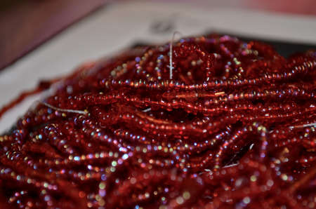 Threaded red beads sitting on a table Stock Photo