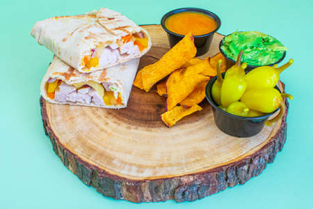 chicken wrap on a trunk-shaped plate, with guacamole and chili peppers