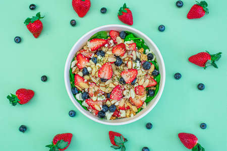 Salad pattern with red berries and green background, healthy concept and vinaigrette.