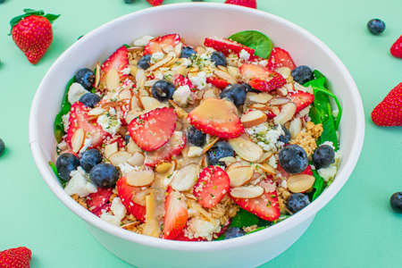 Salad with delicious berries and vinaigrette with green background