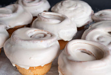 Exquisite freshly baked cinnamon roll covered in white glaze sprinkled with sweet almonds held by one hand.