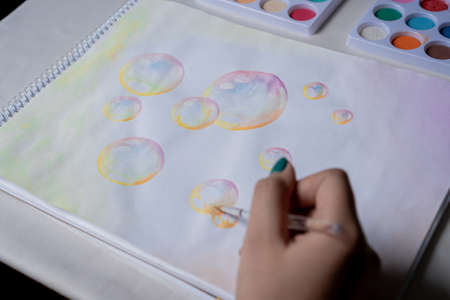 Female hand coloring bubble drawing with colored watercolors in a sketchbook on a white table.