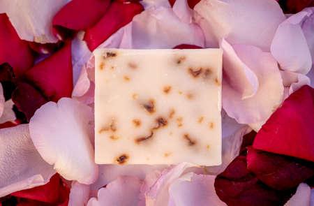 Handmade rose soap with rose petals inside decorated with red and white rose petals on a white background.