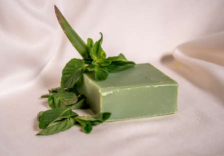 Refreshing green soap made of handmade mint with a branch of mint on top with a white background in close up concept. 写真素材