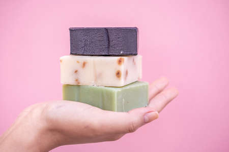 Refreshing soaps handmade of roses, aloe vera and active carbon held in one hand with a pink background and in close up concept.