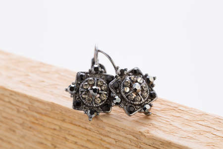 Pair of vintage earrings on a wooden board, studio shot 스톡 콘텐츠