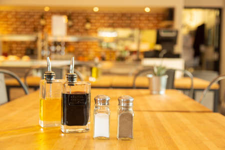 Pepper shaker and salt shaker with bottles of vinegar and oil on a bamboo table Banque d'images
