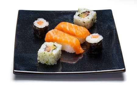 Placa negra con sushi, maki y rollos americanos sobre fondo blanco.