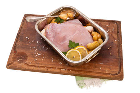 Raw turkey fillet in a stainless steel dish on a white background