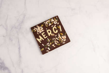 Dark chocolate square with white chocolate thank you note on light background