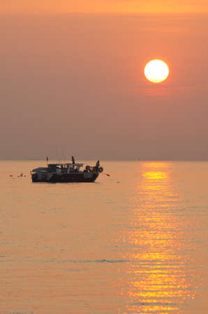 Small fishing boat at sunrise with an orange sky