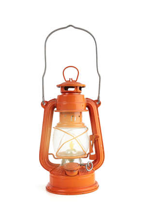 Vintage orange oil lamp with a flame on a white background