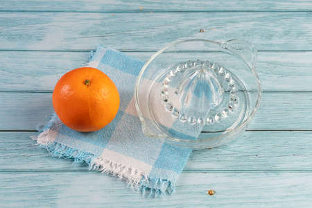 Orange and orange glass press on a blue napkin laid on a blue wooden table