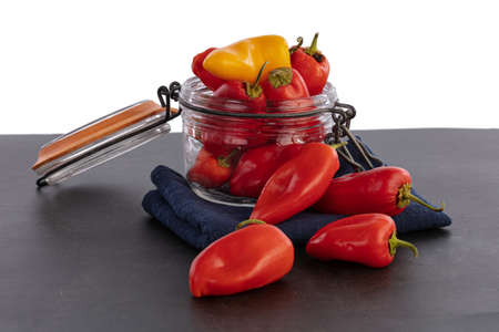 mini bell peppers paprika in a glass jar isolated on white background Standard-Bild