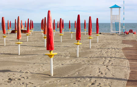 Empty Sandy Beach With Closed Red Umbrellas, a Boardwalk and a Lifeguard Watchtower photo