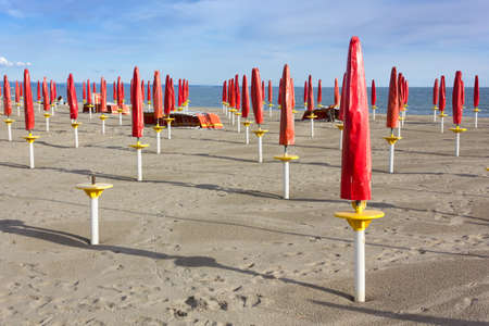 Empty Sandy Beach With Rows of Closed Red Umbrellas photo