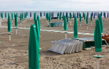 Empty Sandy Beach with Closed Green and Blue Umbrellas photo
