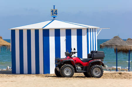 A Red Four-wheeled Beach Vehicle in Front of a Hut on a Sandy Beach photo