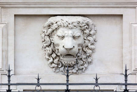 Roaring lion head high-relief on the facade of a palace photo