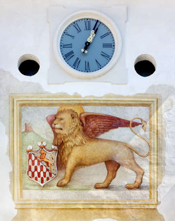 st mark: Venetian Winged Lion Fresco and Clock on West Tower Town Gate in Spilimbergo, Italy Stock Photo