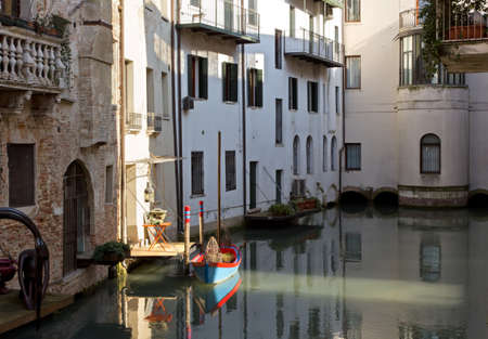 treviso: Little Boat Docked Among Houses in Treviso, Italy Stock Photo