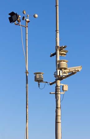 pluviometro: Dos polos con diversos calibres y dispositivos contra un cielo azul