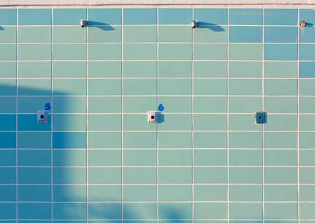 pay wall: Blue tiled numbered outdoor beach showers