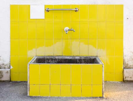 tiled: Outdoor yellow tiled washbasin