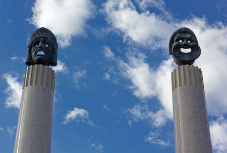 Bronze sculptures of ancient greek theater masks on the top of two marble columns