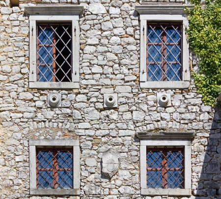 drystone: Facade of a medieval castle with drystone wall and windows