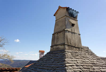 slate roof: Smoking chimney over a traditional slate roof