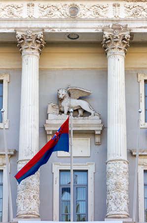 leon con alas: Veneciana escultura de le�n con alas y la bandera de la ciudad en la fachada del ayuntamiento en Piran, Eslovenia