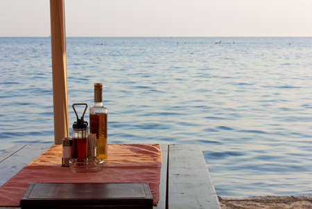 dinner menu: Set restaurant wooden table in front of the sea