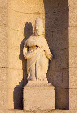 country church: Saint Blaise statue on the facade of a country church at sunset Stock Photo