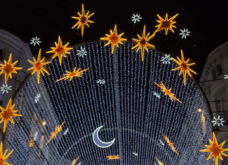 electric avenue: Street Christmas lights over a boulevard with moon and stars Stock Photo