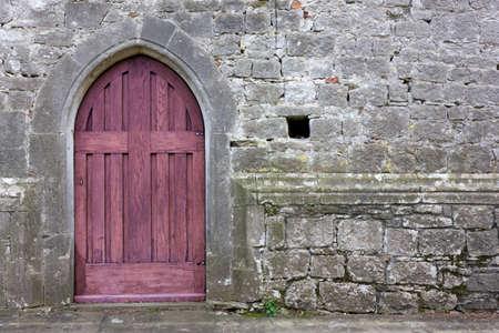 christian religion: Old purple gothic church back door Stock Photo