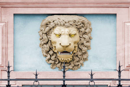 neoclassic: Roaring lion head colored high-relief on the facade of a palace