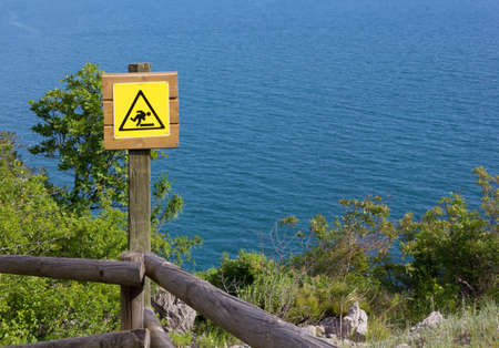 wooden trail sign: Yellow danger sign over the wooden fence of a seaside panoramic trail Stock Photo