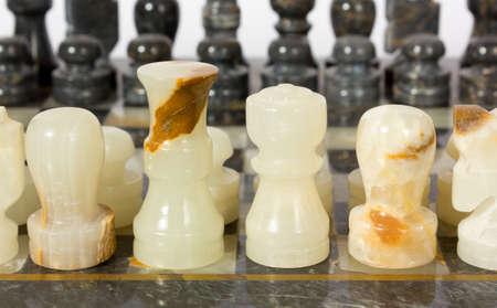 chessmen: Black and white marble chessmen on a chessboard