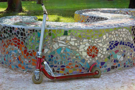 play the old park: Old kick scooter leaned against a colored mosaic wall in a park