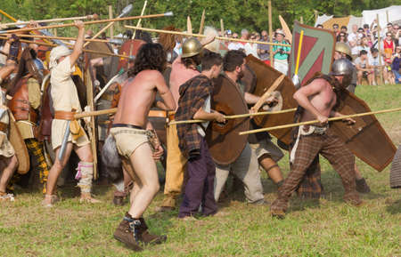 celts: AQUILEIA, Italy - June 22, 2014: View of a celtic formation in action in the battle between the Romans and the Carnic Celts at the ancient roman reenactment.