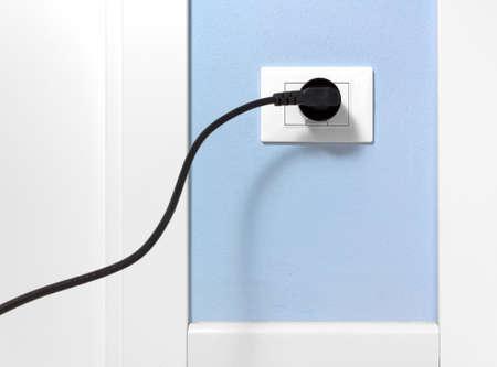enchufe de luz: Enchufe negro insertado en una toma de corriente en una pared interior de color azul claro Foto de archivo
