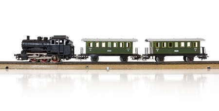 Vintage model electric train formed by a steam locomotive and two passenger cars on the rails Stock Photo