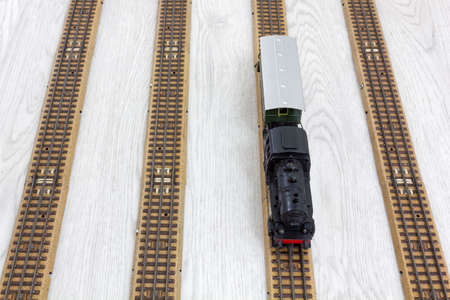 Vintage model electric train formed by a steam locomotive and a passenger car on the rails over a wooden textured floor Stock Photo