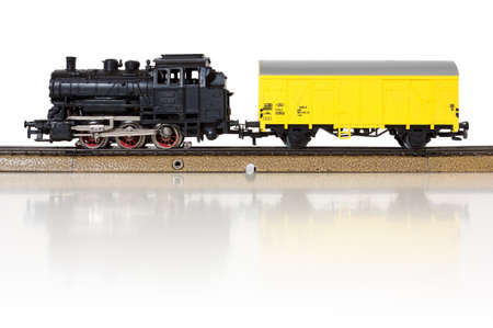 Model electric freight train formed by a vintage steam locomotive and a yellow boxcar on the rails